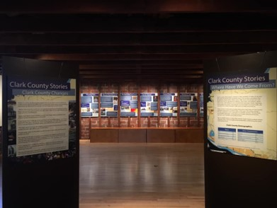 Open room, signage on left and right leading walkway to more signage in background, Clark County Historical Museum Exhibit