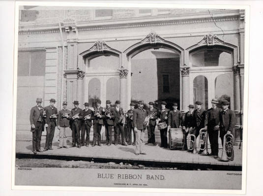 """Line of men wearing uniforms, holding instruments, one man standing in front, text """"Blue Ribbon Band"""", grayscale photograph"""