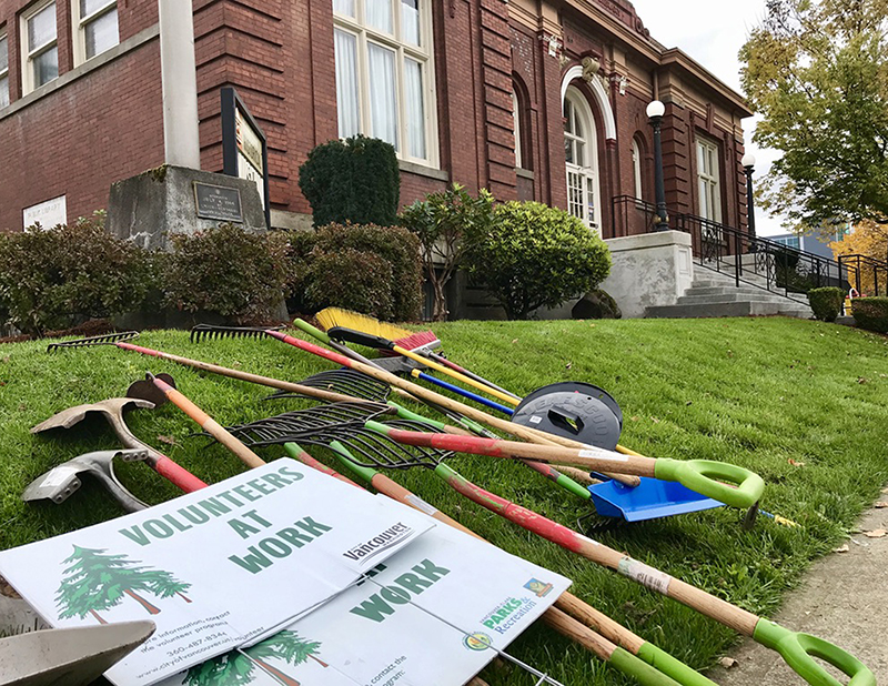 Volunteer signs, shovels and rakes lay in grass of brick Clark County Historical Museum