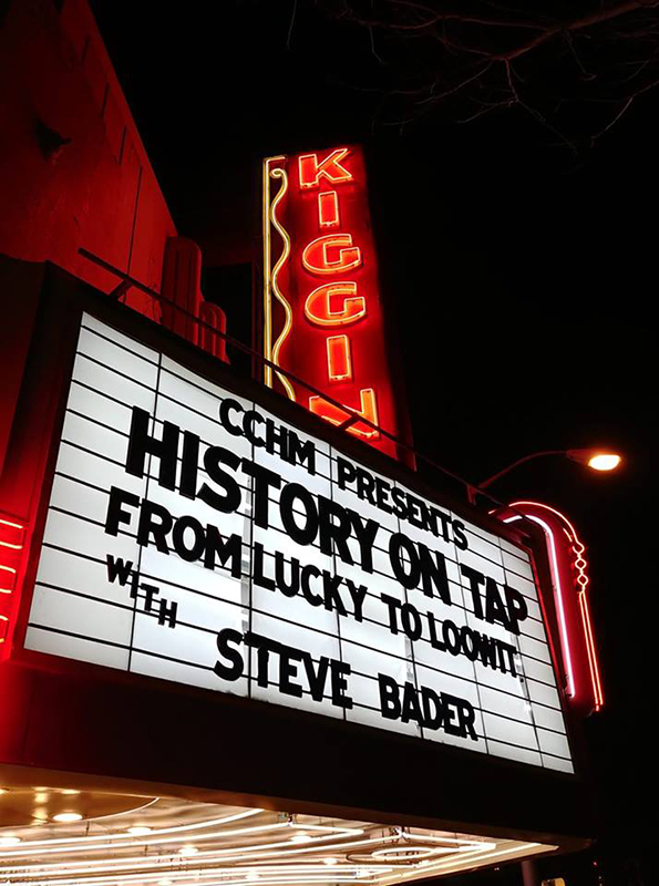 """Outside Kiggins Theater marquee at night with neon lighting, black text """"History on Tap"""""""