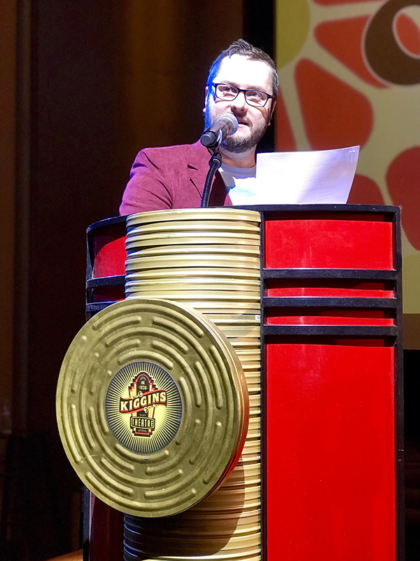 Speaker in suit standing behind red and gold podium, Kiggins Theater