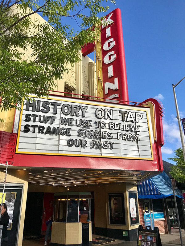 """Outside Kiggins Theater marquee and ticket booth, black text """"History on Tap"""""""