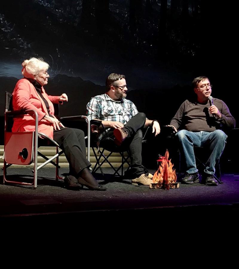 One woman and two men sitting in camping chairs on stage, fake fire in front, digital night landscape in background