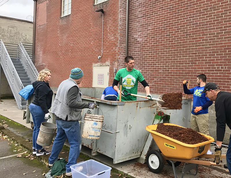 Man standing in large dumpster shoveling out dirt, others surround with buckets and wheelbarrow