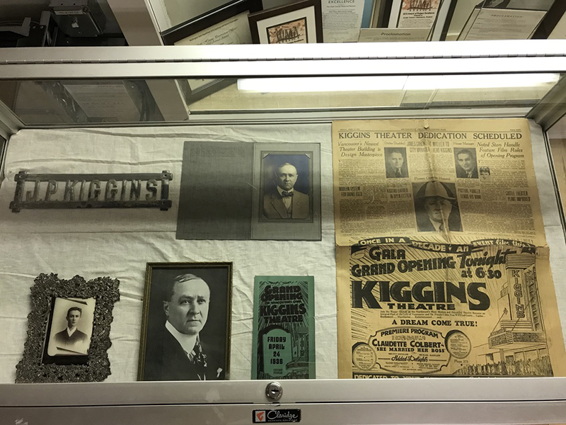 Glass display case holding images of individuals & local newspaper pages on white background, Clark County Historical Museum