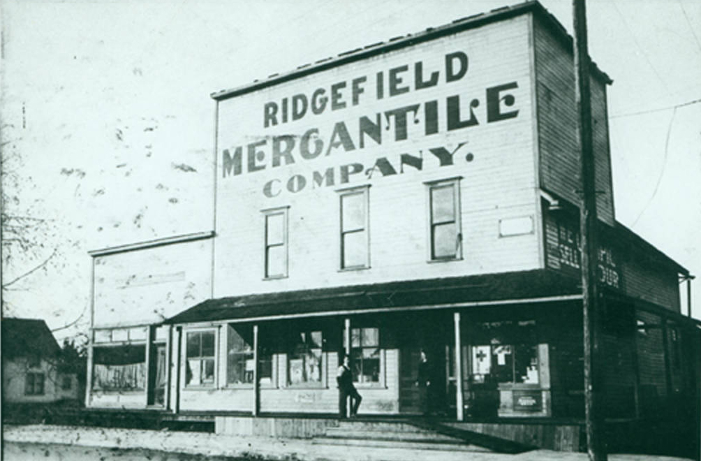 """Wood building with wood awning, person standing out front, text on building reads """"Ridgefield Mercantile Company"""", greyscale"""