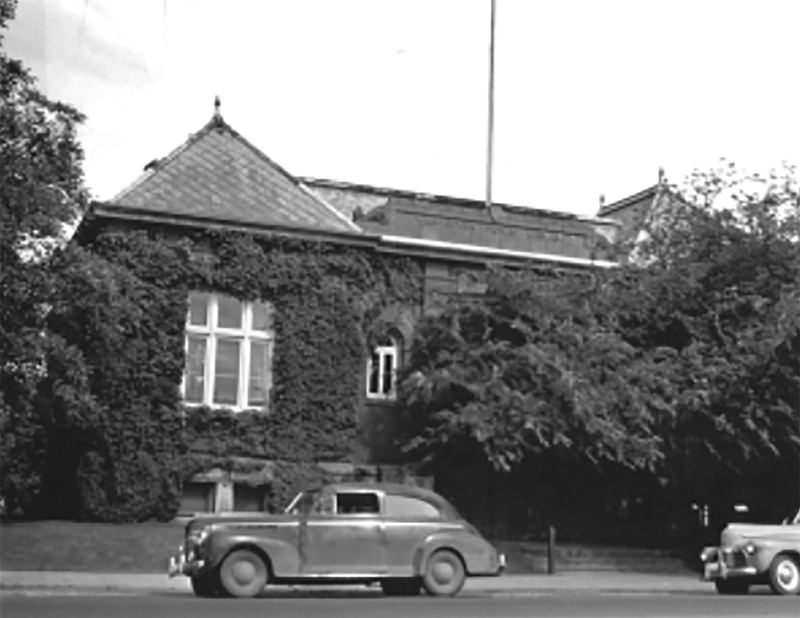 Old car parked out front of ivy covered brick Clark County Historical Museum, old photograph