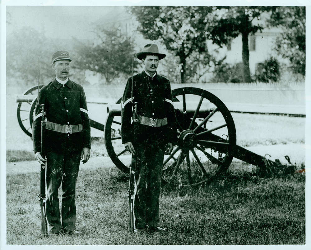 Two men in military uniform standing at attention holding muskets, cannon in background, greyscale