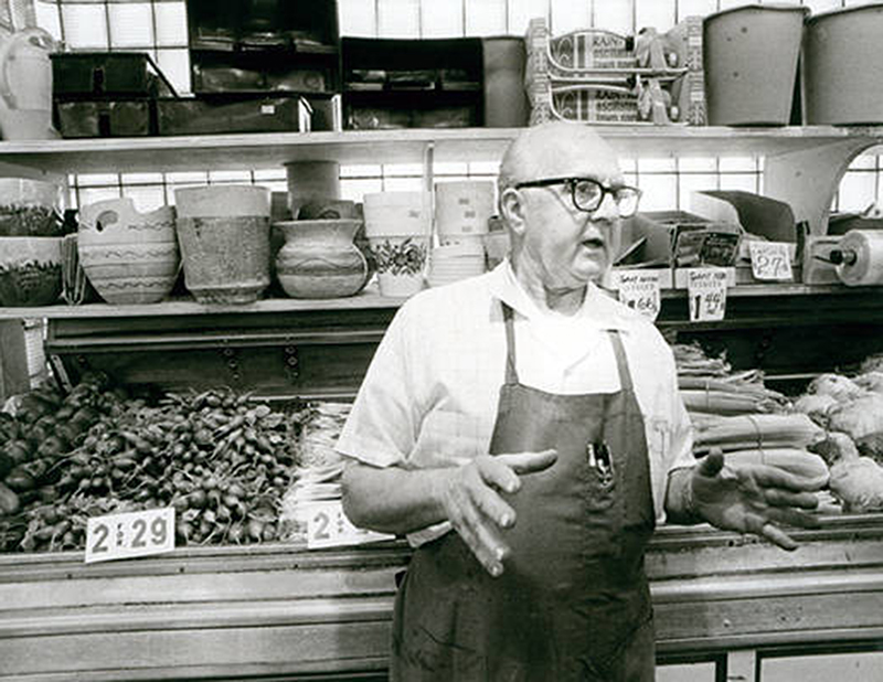 Man in apron and glasses talking produce lined behind him