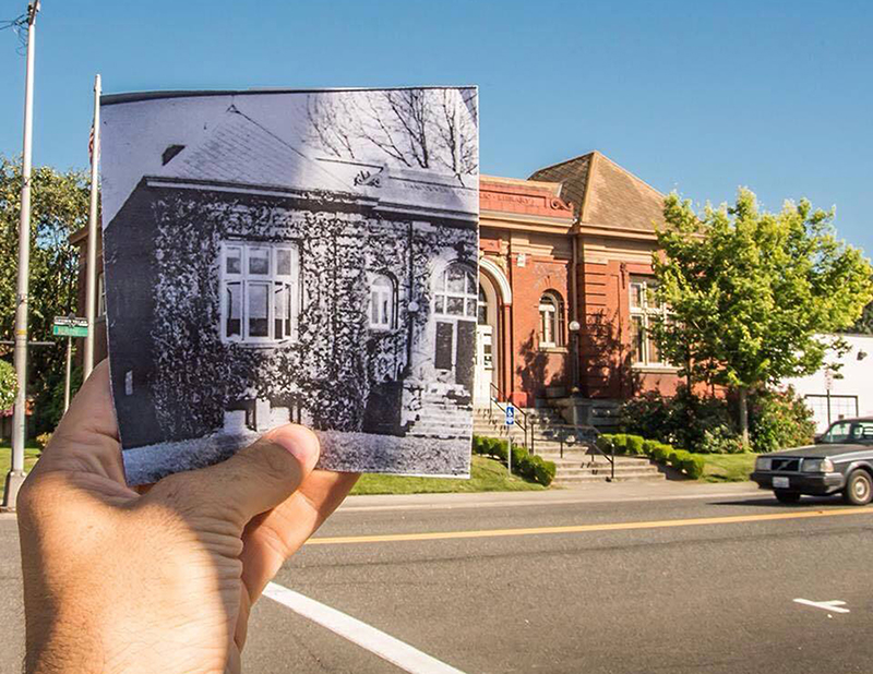 Hand outside holding grayscale image of brick building over street view of building, Clark County Historical Museum